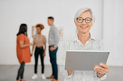 Buy stock photo Portrait of a senior businesswoman using a digital tablet in a modern office with her colleagues in the background