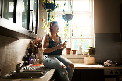 Buy stock photo Shot of a young woman using a smartphone in the kitchen at home