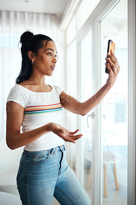 Buy stock photo Cropped shot of an attractive young blogger standing in her home and using her cellphone to record a vlog