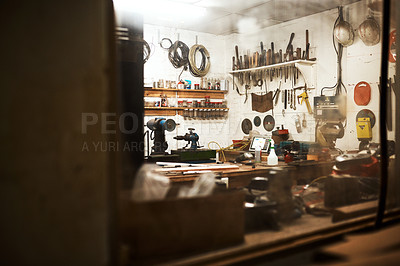 Buy stock photo Shot of a workshop filled with different types of tools inside someone's home at night