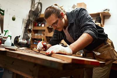 Buy stock photo Cropped shot of a focused young carpenter doing measurements on a piece of wood inside of a workshop at night