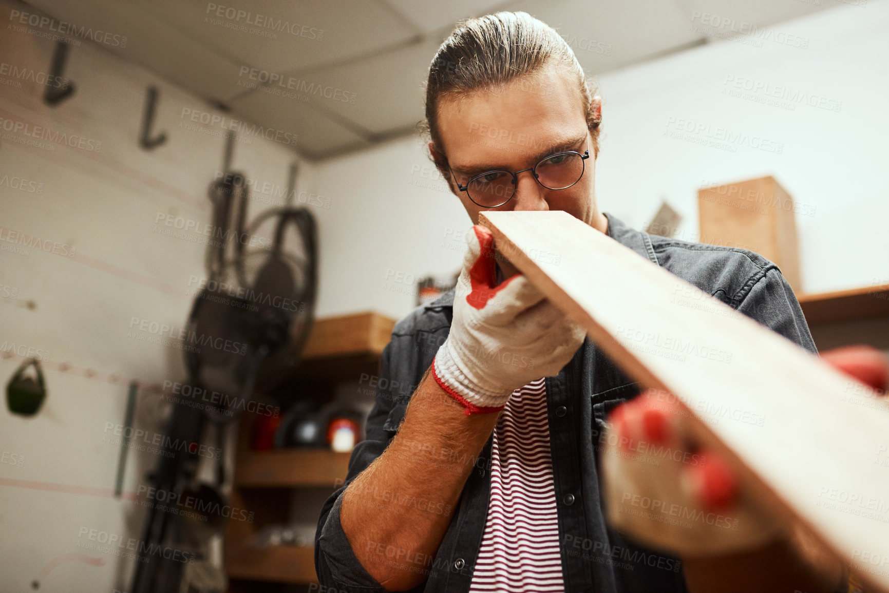 Buy stock photo Cropped shot of a focused young male carpenter looking down the surface of a piece of wood that he sanded down inside of his workshop