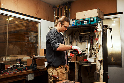 Buy stock photo Cropped shot of a focused young male carpenter opening a toolbox to use while working inside of a workshop at night