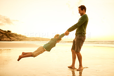 Buy stock photo Shot of a man spending the day at the beach with his young son