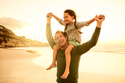 Buy stock photo Shot of a man carrying his daughter on his shoulders at the beach