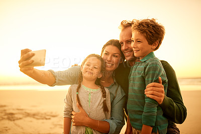 Buy stock photo Cropped shot of a family of four taking a selfie on the beach