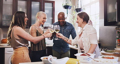 Buy stock photo Shot of a group of young friends toasting with wine while preparing a festive meal at home