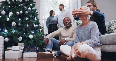 Buy stock photo Shot of a young woman receiving a surprise Christmas present from friends