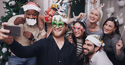 Buy stock photo Shot of a group of young friends wearing funny hats and taking selfies at a Christmas party