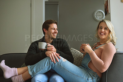 Buy stock photo Shot of a young couple enjoying a coffee break together on the sofa at home
