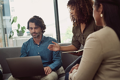 Buy stock photo Shot of a group of businesspeople working together on a laptop in an office