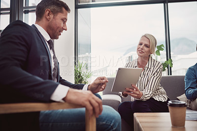 Buy stock photo Shot of two mature businesspeople working together on a digital tablet in an office
