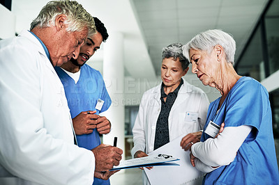 Buy stock photo Cropped shot a mature male doctor writing on a file while having a meeting with his team in a hospital