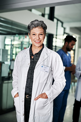 Buy stock photo Cropped portrait of an attractive mature female doctor smiling while standing in a hospital with her colleagues in the background
