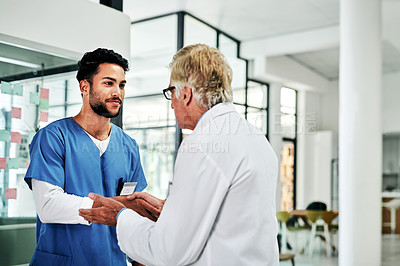Buy stock photo Cropped shot of a handsome young male nurse shaking hands with a mature doctor in a hospital