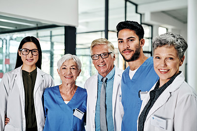 Buy stock photo Cropped portrait of a diverse group of medical practitioners smiling while standing together in a hospital