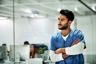 Buy stock photo Cropped shot of a handsome young male doctor looking thoughtful while standing with his arms crossed in a hospital