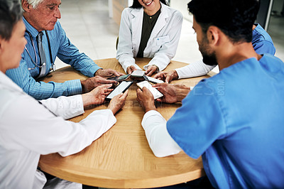Buy stock photo Cropped shot of a diverse group of medical practitioners using their smartphones together during a meeting in a hospital