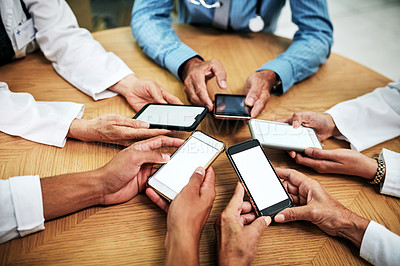 Buy stock photo Cropped shot of a group of unrecognizable medical practitioners using their smartphones together during a meeting in a hospital