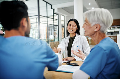 Buy stock photo Cropped shot of an attractive young female doctor shaking hands with a male nurse during an introduction in a hospital