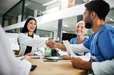 Buy stock photo Cropped shot of medical practitioners shaking hands during a meeting in a hospital