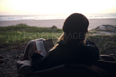 Buy stock photo Rearview shot of a young woman reading a book outdoors