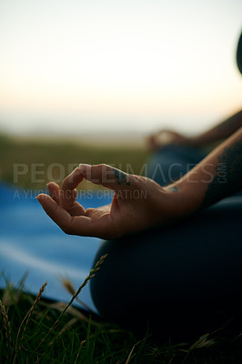 Buy stock photo Cropped shot of an unrecognizable woman sitting alone and meditating during a relaxing day outdoors
