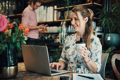 Buy stock photo Cropped shot of an attractive young businesswoman sitting and using her laptop while enjoying a cup of coffee