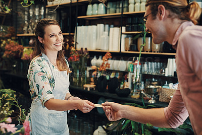 Buy stock photo Cropped shot of an attractive young businesswoman standing in her floristry and accepting a customer's credit card for a payment