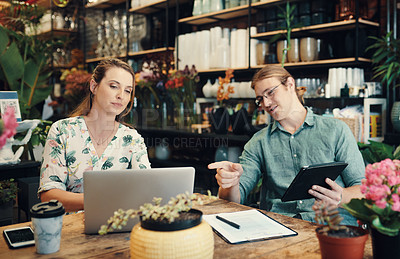 Buy stock photo Cropped shot of two young businesspeople sitting and working on technology during a discussion in their floristry