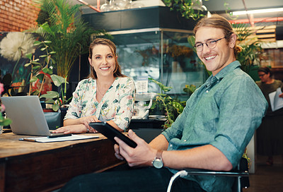 Buy stock photo Cropped portrait of two young businesspeople sitting and working on technology during a discussion in their floristry