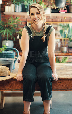 Buy stock photo Cropped portrait of an attractive young businesswoman sitting alone in her flower shop during the day