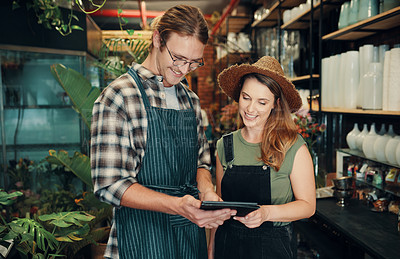 Buy stock photo Cropped shot of two young business owners standing in their floristry together and using a tablet