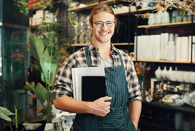 Buy stock photo Cropped portrait of a handsome young business owner standing in his floristry alone and holding paperwork and a tablet