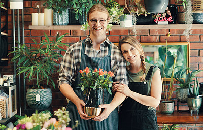 Buy stock photo Cropped portrait of two young business owners standing in their floristry together while holding a bouquet of roses