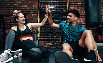 Buy stock photo Cropped shot of two cheerful young sportspeople high fiving each other while taking a break in a gym