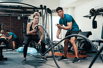 Buy stock photo Cropped shot of an attractive young sportswoman working out with battle ropes with her personal trainer in a gym