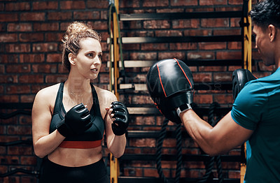 Buy stock photo Cropped shot of an attractive young female boxer working out with her personal trainer in a gym