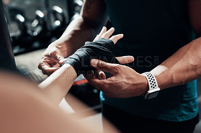 Buy stock photo Cropped shot of an unrecognizable sportswoman getting her hand wrapped by her personal trainer in a gym