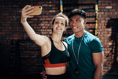 Buy stock photo Cropped shot of two young sportspeople taking a selfie together in a gym