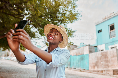 Buy stock photo Cropped shot of an attractive young woman taking a self portrait with her cellphone outside during the day