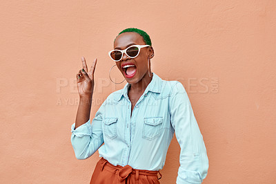 Buy stock photo Cropped shot of a cheerful young woman posing while showing the peace sign against a orange background