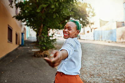 Buy stock photo Portrait of a cheerful young woman looking back at the camera while holding her hand out during the day