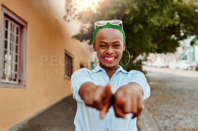 Buy stock photo Portrait of a cheerful young woman pointing to the camera while walking around outside during the day