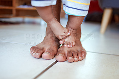Buy stock photo Cropped shot of an unrecognizable father's feet and his baby's feet at home
