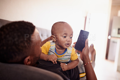 Buy stock photo Shot of a young man using a smartphone while relaxing on the sofa with his baby boy