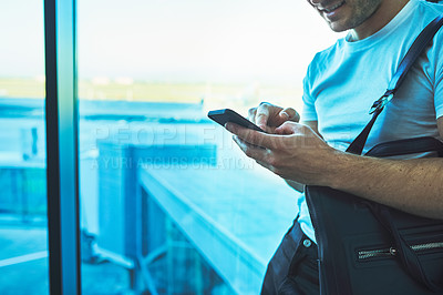 Buy stock photo Cropped shot of a young man using a smartphone in an airport