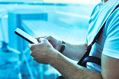 Buy stock photo Cropped shot of a man using a smartphone in an airport