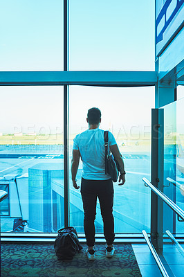 Buy stock photo Rearview shot of a young man looking thoughtfully out of an airport window