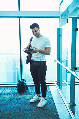 Buy stock photo Shot of a young man getting his passport and boarding pass ready before his flight at an airport